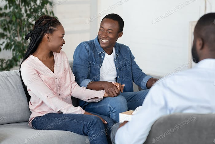 Happy african american couple visiting social worker before adoption