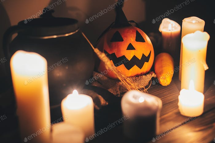 Jack o lantern pumpkin with candles, bowl, witch broom and bats, ghosts