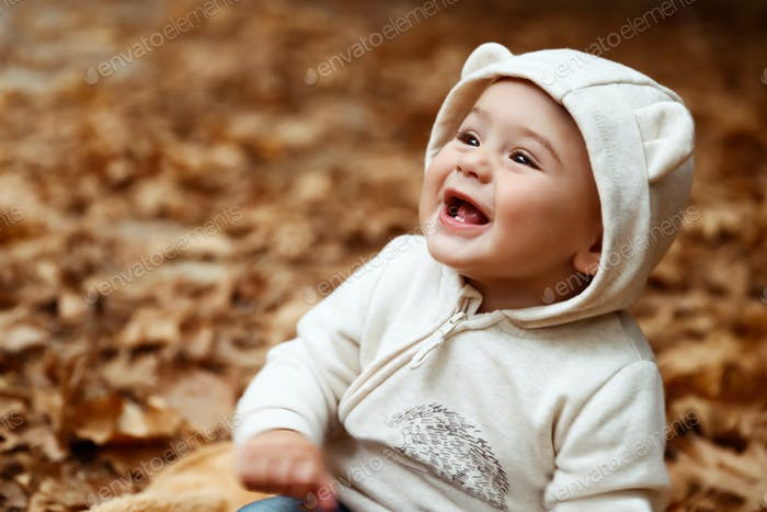 Cheerful baby in autumn forest