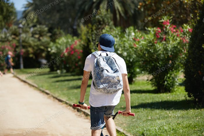 Extreme sport. Back view of hipster 15-year old teenage boy wearing cap and carrying backpack, cycli