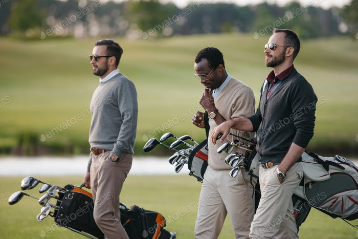 multiethnic golfers holding bags with golf clubs and walking on golf course