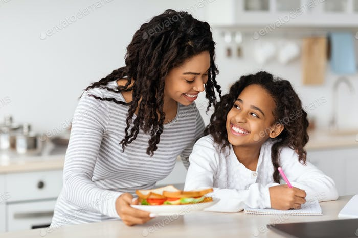 Cute black mother and daughter eating sandwiches