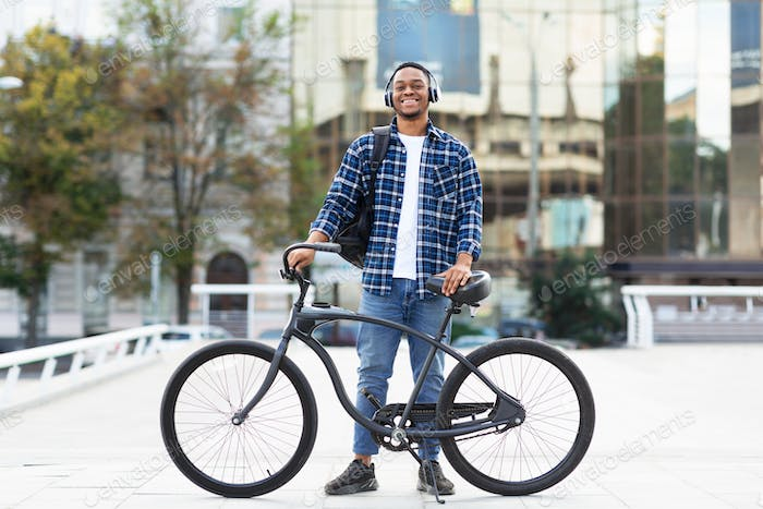 Portrait of african american guy standing with his bike