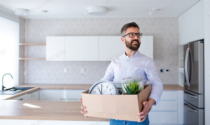 Mature man standing in unfurnished house, holding a moving box.