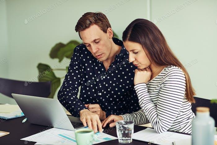 Zwei Bürokollegen sitzen an einem Schreibtisch und diskutieren gemeinsam Papierkram