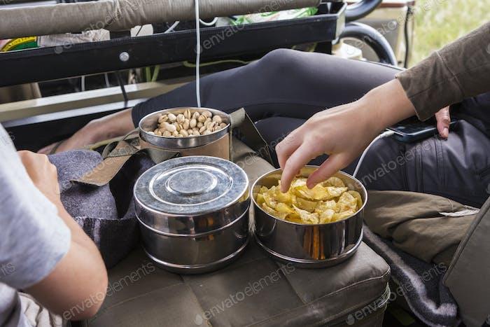 Hände greifen nach Snacks in Safari-Fahrzeug