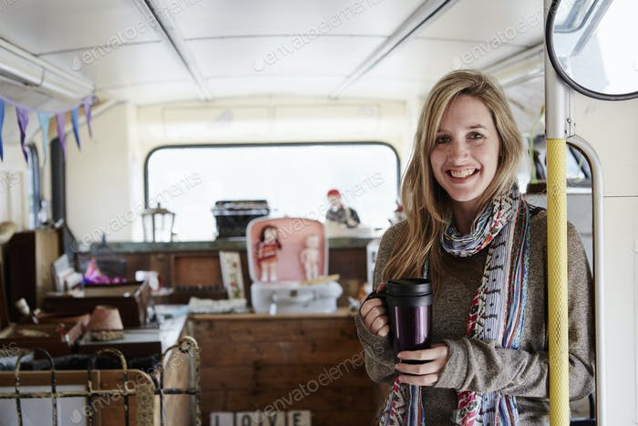 A woman standing in a bus converted into a vintage shop