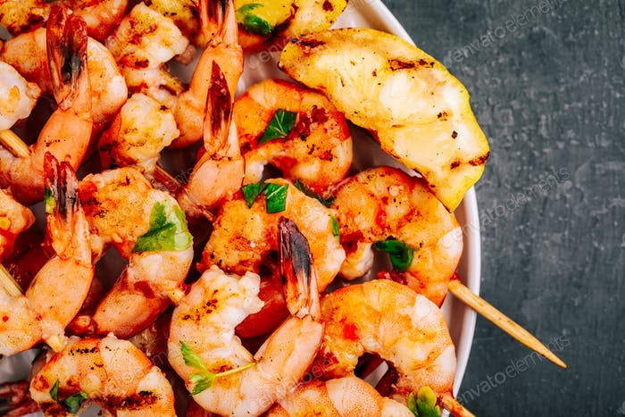 Sweet Chili Shrimp Skewers with lemon and parsley on gray stone background