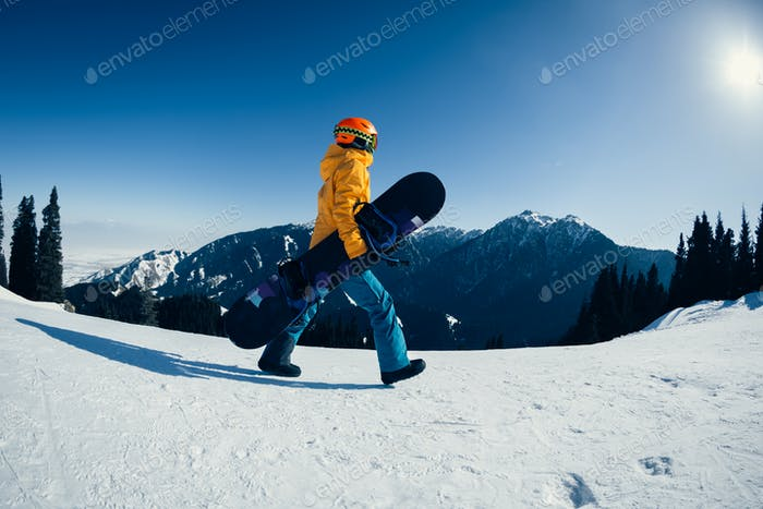 Snowboarder walking on alpine mountain top
