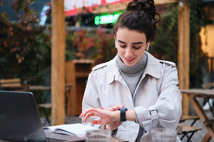 Pretty smiling brunette girl in trench coat happily using smartwatch studying in cafe on city street