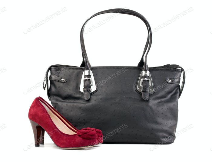 Pair of red female shoes and black handbag over white