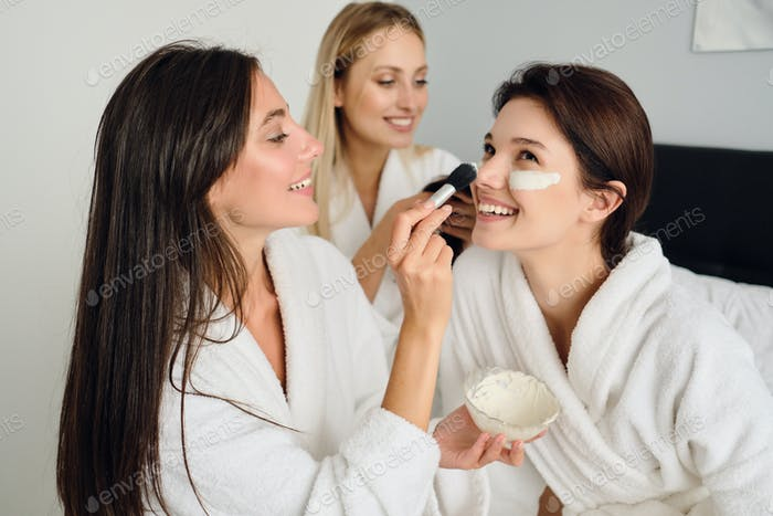Three young beautiful women in white bathrobes sitting on bed happily making cosmetic mask together