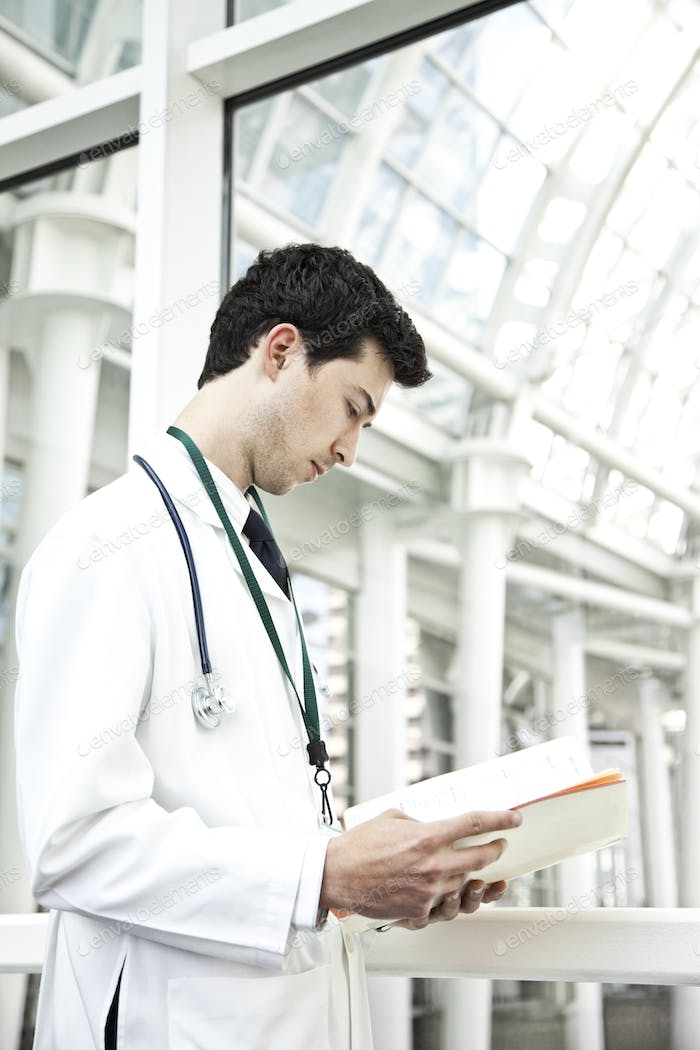 Caucasian man doctor going over a patient history.