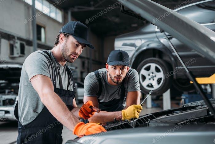 professionelle Arbeiter reparieren Auto im Mechanikergeschäft
