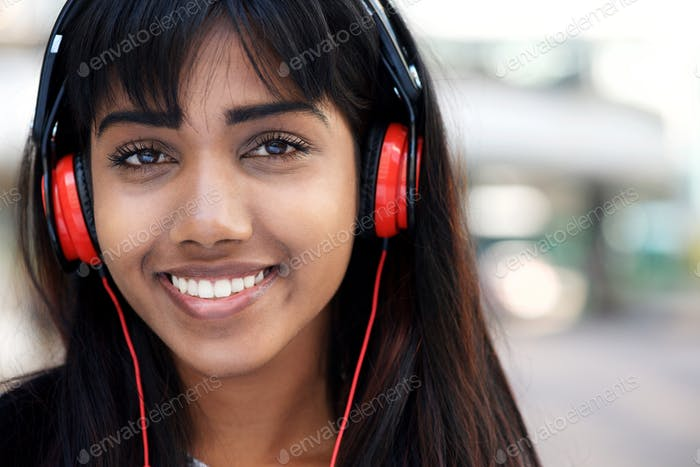 Close up young Indian woman smiling with headphones