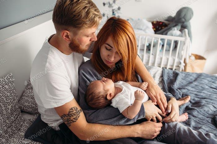 Glückliche Familie mit neugeborenen Baby auf dem Bett