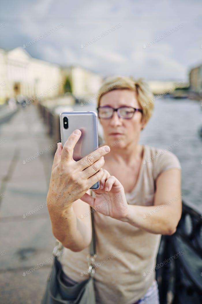 Senior female taking selfie on embankment