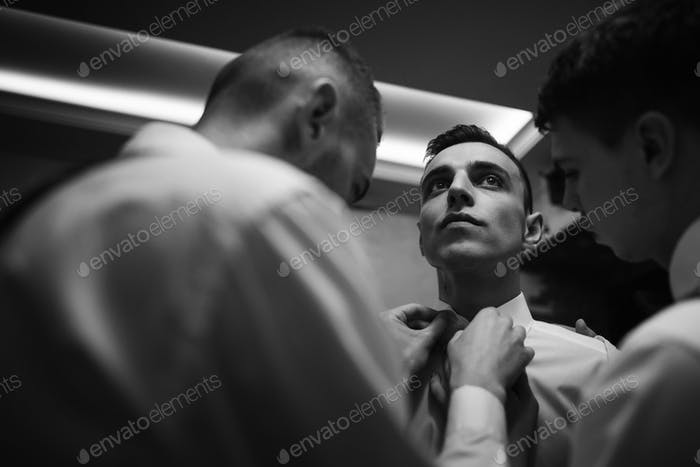 Handsome groomsman friends helping groom put on stylish white shirt
