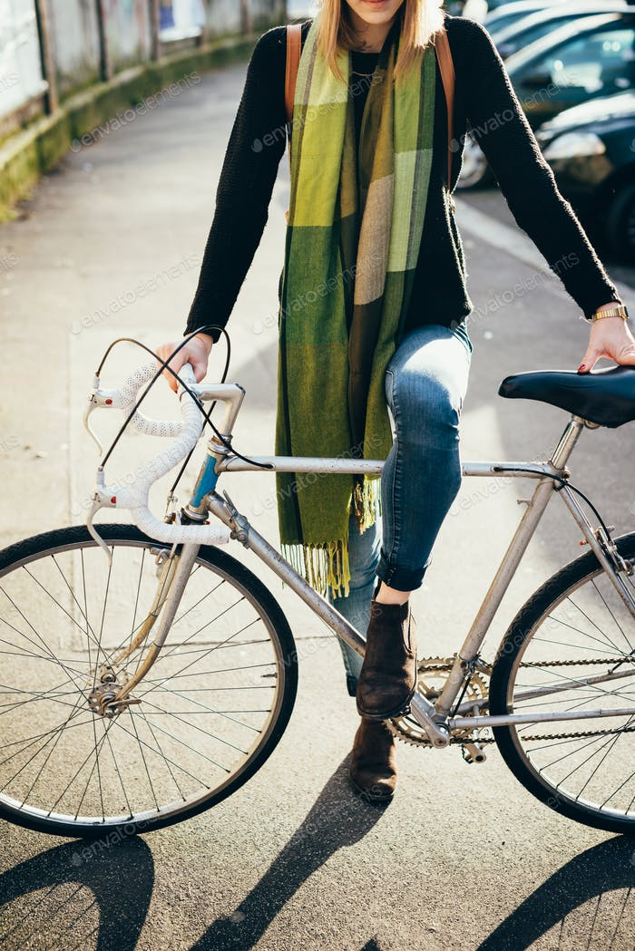 From the neck down view of a young woman holding a bicycle outdo