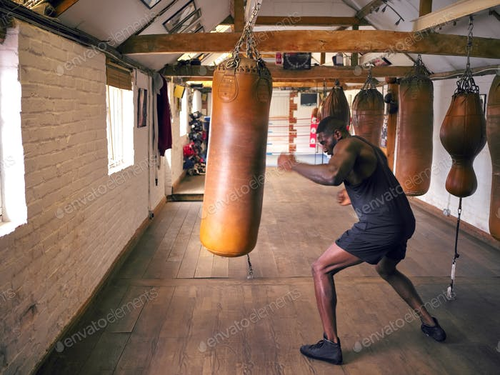 Action Shot Of Male Boxer In Gym Training Mit Leder Boxsäcke