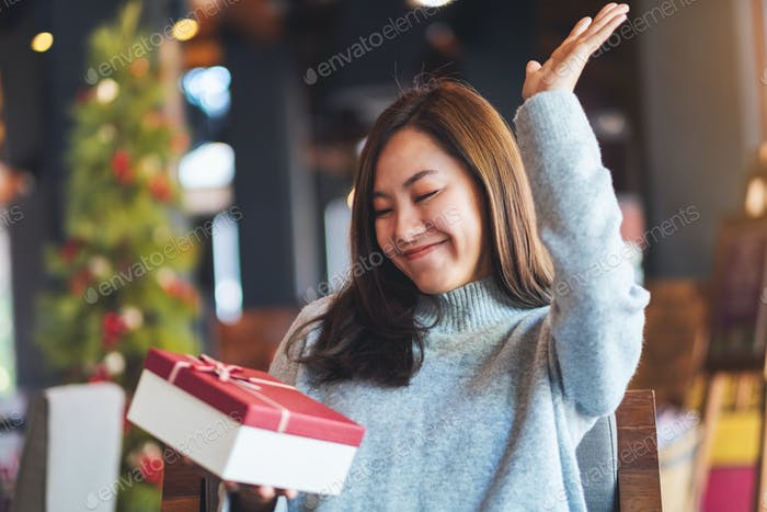 Happy young woman receiving a gift box