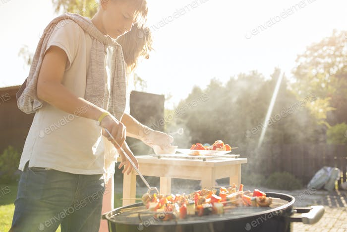 Teenage boy (12-13) barbecuing at garden party