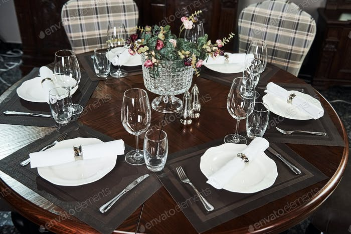Picture of served table with glasses, plant and silver colored forks and knives