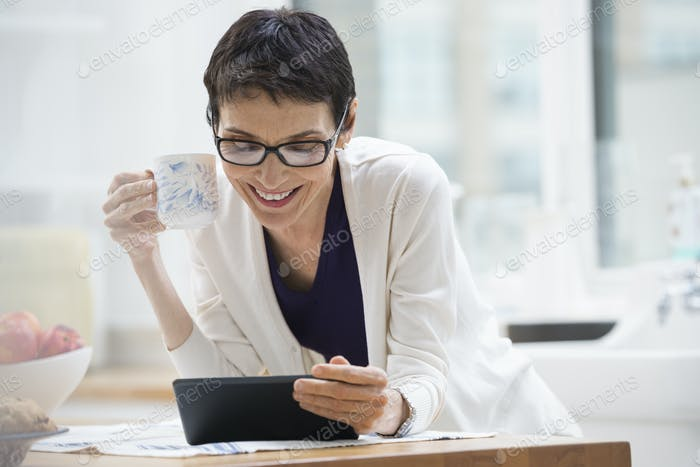 Woman dressed for work in cream jacket,checking her digital tablet.