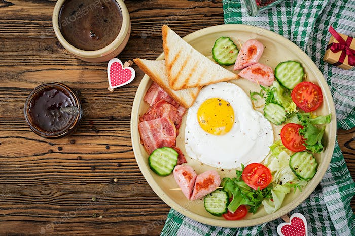 Breakfast on Valentine's Day - fried egg in the shape of a heart, toasts, sausage