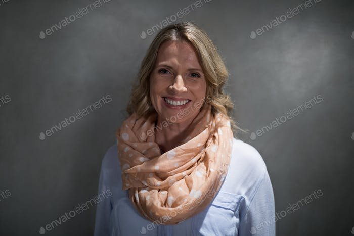 Portrait of beautiful woman smiling against grey background