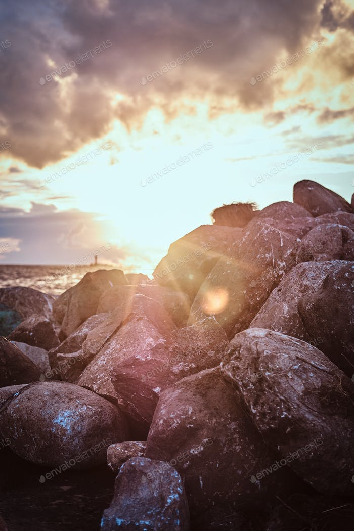 Beautiful seaside with stones, against the background of the amazing bright sunset.