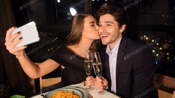 Happy romantic couple making selfie photo on cellphone