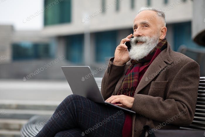 Elderly businessman with laptop sitting on bench, talking on phone