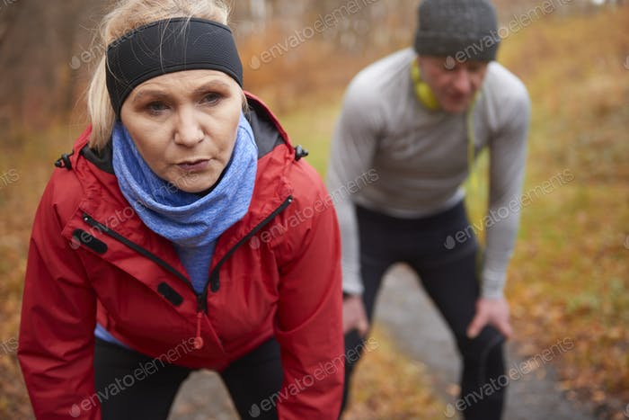 Senior couple exercising in the autumnal forest
