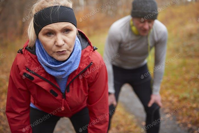 Seniorenpaar trainieren im herbstlichen Wald