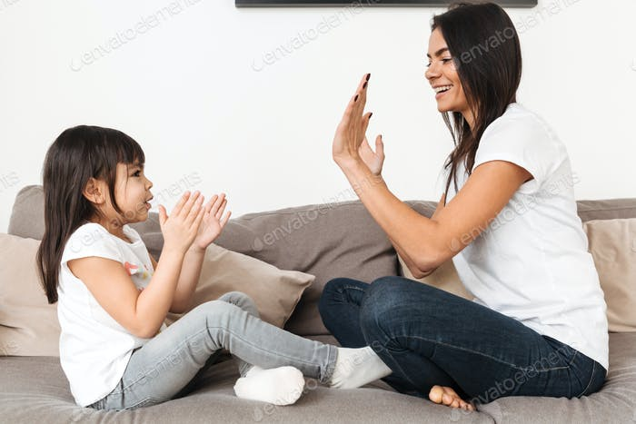 Portrait of cheerful family mother and girl playing together pat