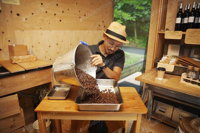 Hombre japonés con sombrero y gafas sentado en un Eco Cafe, vertiendo granos de café recién tostados