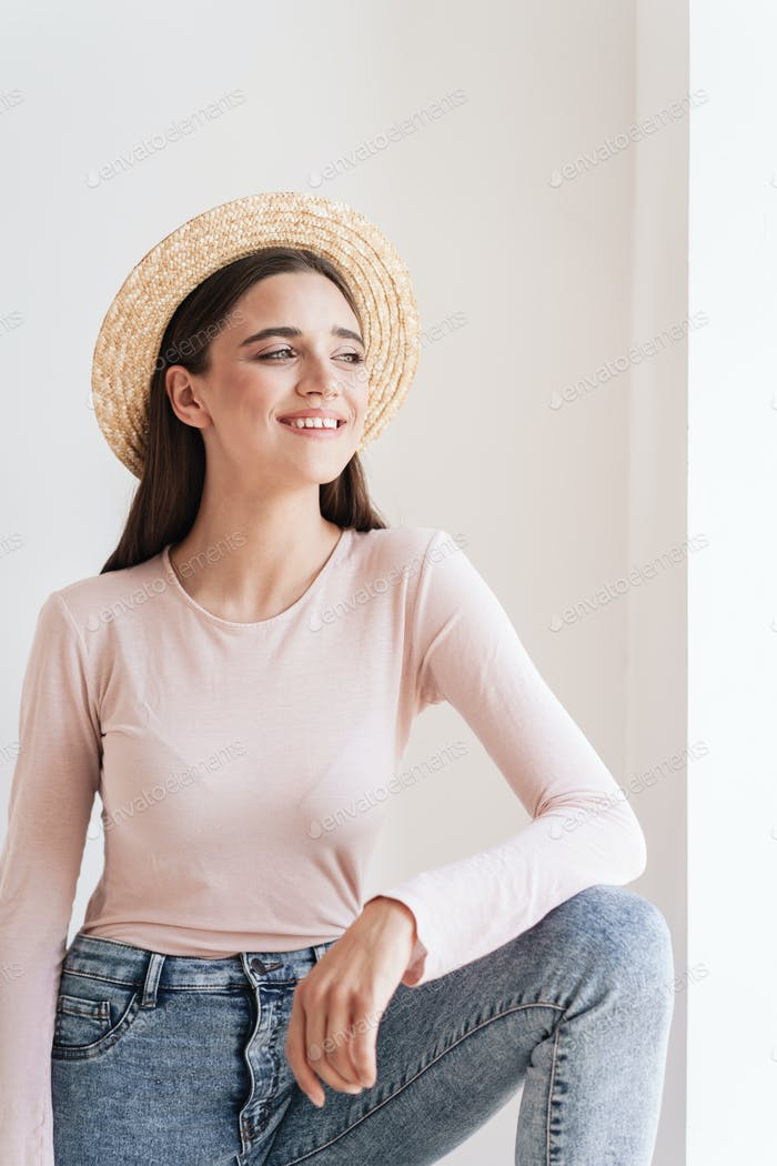 Portrait of a laughing young brunette girl in straw hat looking away