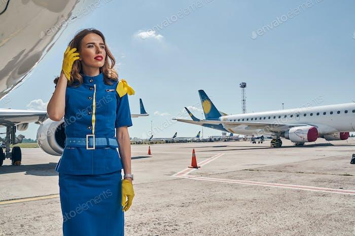 Slender Caucasian stewardess gazing into the distance