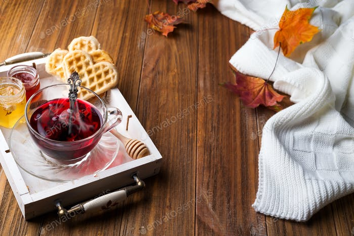 autumn fall concept with knitted blanket and hot tea with waffer, jam, honey on wooden tray on
