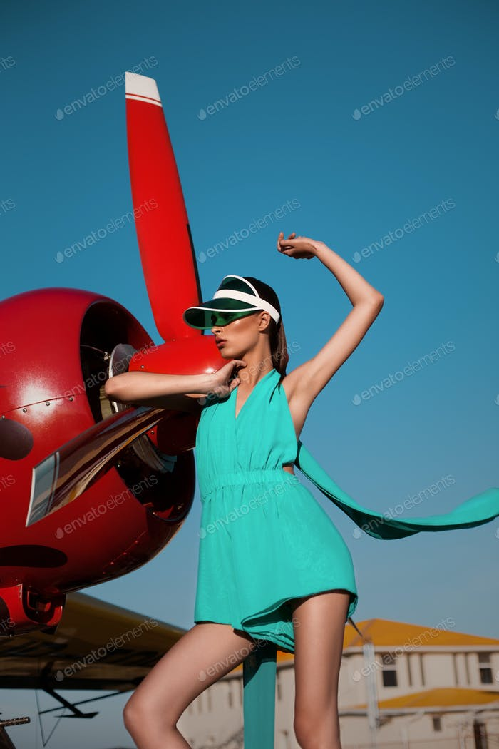 Fashion girl as a pilot in a visor next to propeller plane during sunset