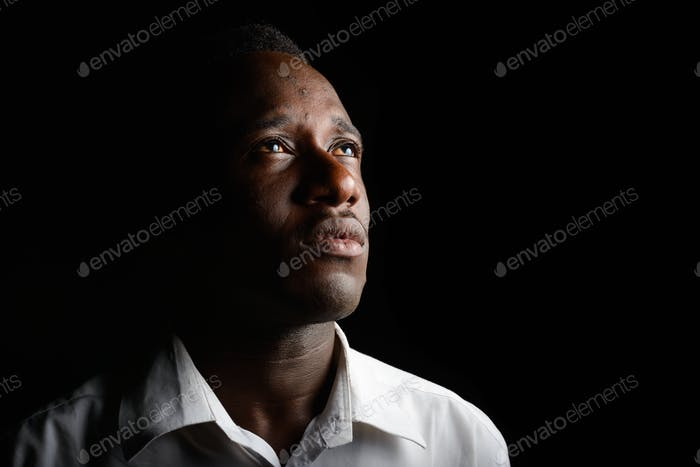 Young African businessman in the dark against black background