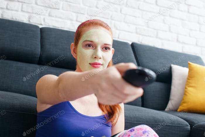 Girl With Beauty Mask Watching Television At Home