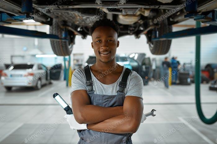 Male worker checks car suspension, auto service