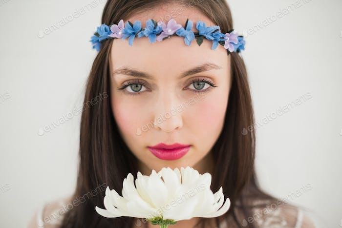 Pretty hippie smelling a flower against a grey wall