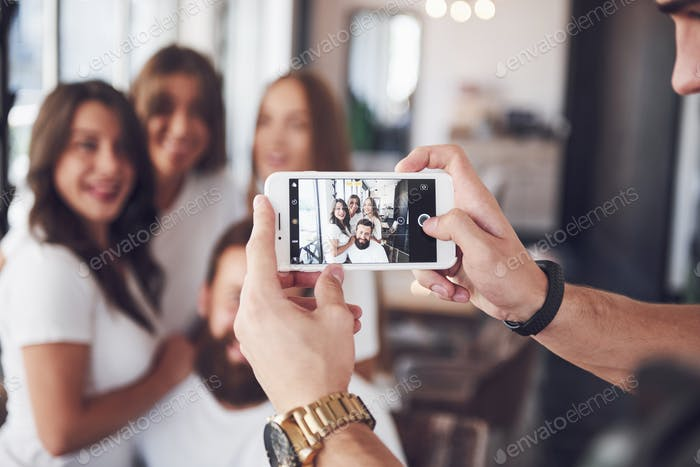 Blur portrait of blissful young best friends with hands holding phone on foreground
