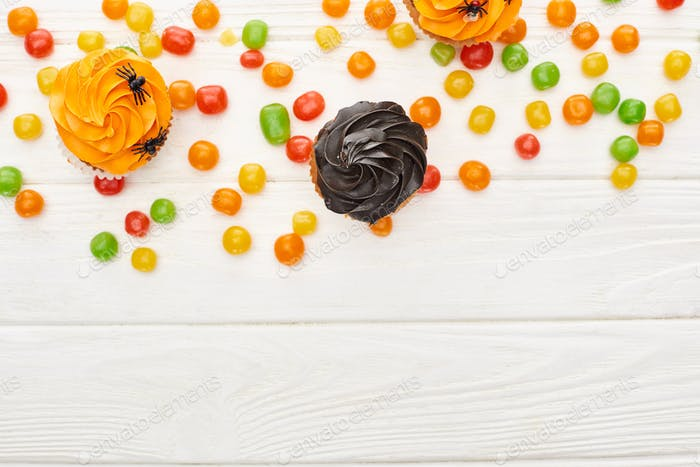 Top View of Colorful Bonbons And Cupcakes on White Wooden Table, Halloween Treat