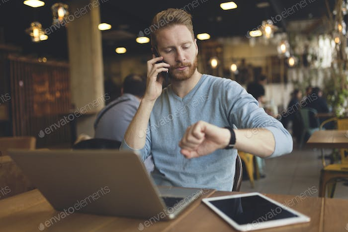 Young busy man having phone call in cafe