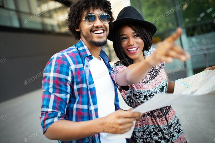 Happy black couple on vacation sightseeing city with map