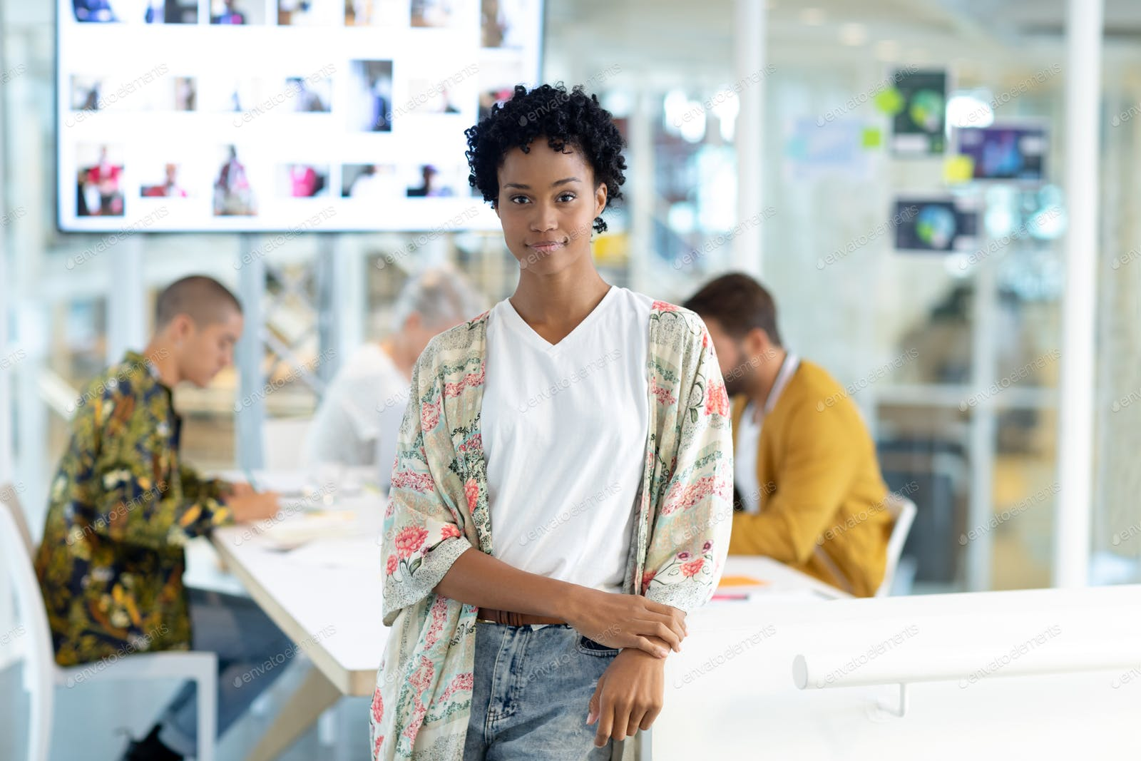 African American Female Fashion Designer Leaning On A Table While Diverse Business People Discussing Photo By Wavebreakmedia On Envato Elements